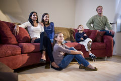 Interracial family sitting on sofa watching TV. Interracial family of five sitting together on living room sofa watching television Royalty Free Stock Photography