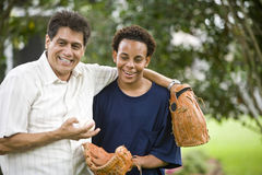 Interracial father and son with baseball gloves stock images