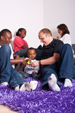 Interracial friends and family. Young group of multiracial friends - two young families enjoying an afternoon at home Stock Image