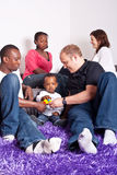 Interracial friends and family. Young group of multiracial friends - two young families enjoying the afternoon royalty free stock images
