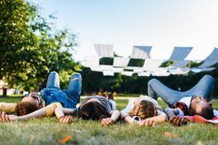 interracial friends resting on green lawn royalty free stock photography