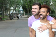 Happy gay couple holding hands watching sunset on the beach Interracial gay couple outdoor close up