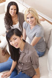 Interracial Group of Beautiful Women Friends. Interracial group of three beautiful young women friends at home sitting together on a sofa smiling and having fun Stock Photos