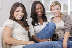 Interracial Group of Beautiful Women Friends. Interracial group of three beautiful young women friends at home sitting together on a sofa smiling and having fun Royalty Free Stock Photo