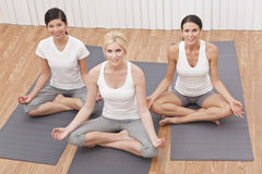 Interracial Group of Beautiful Women Yoga Position. An interracial group of three beautiful young women sitting cross legged in a yoga position at a gym stock photography