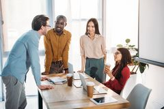 Interracial group of business colleagues discussing work during coffee break at workplace. In office royalty free stock photography