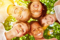 Interracial group of kids smiling. And putting heads together as team royalty free stock images