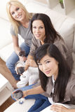 Interracial Group Three Women Drinking Wine. Interracial group of three beautiful young women friends at home drinking red wine together stock image