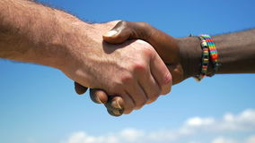 Interracial handshake on sky background