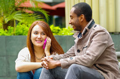 Interracial happy charming couple sitting on steps in front of building interacting and smiling for camera Stock Photos
