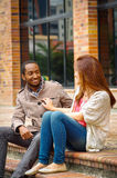 Interracial happy charming couple sitting on steps in front of building interacting and smiling for camera Royalty Free Stock Images