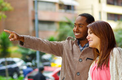 Interracial happy charming couple wearing casual clothes interacting for camera in outdoors urban environment Royalty Free Stock Photos