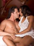 Interracial heterosexual sensual couple in bed Stock Image