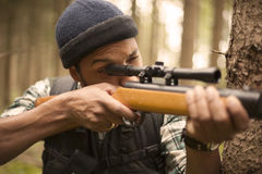Interracial hunter in the forest aiming at prey Stock Images