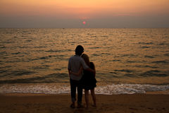 A Interracial lover Couple hug. Ing on the beach watching sunset Royalty Free Stock Images