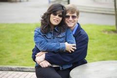 Interracial par som utomhus kramar Royaltyfria Bilder