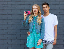 Interracial young couple in love outdoor. Stunning sensual outdoor portrait of young stylish fashion couple posing in summer. Girl. Interracial very young couple Royalty Free Stock Photography