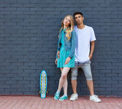 Interracial young couple in love outdoor whis skateboard. Stunning sensual outdoor portrait of young stylish fashion couple posing Stock Photo