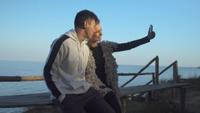 Interracial young couple in love makes selfie sitting on a wooden bench in the sunshine on the background of a lake. Interracial young couple makes selfie stock video