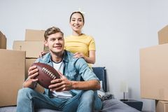 interracial young couple sitting on bed with american football ball after moving into