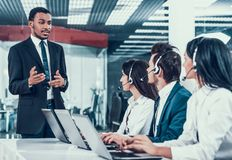 Interracial young happy employees in call center stock photography
