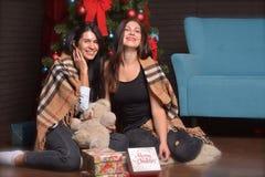 Interrior del Año Nuevo la mujer feliz se está sentando en el piso cubierto en manta Fotografía de archivo