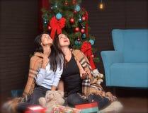 Interrior del Año Nuevo la mujer feliz se está sentando en el piso cubierto en manta Foto de archivo libre de regalías