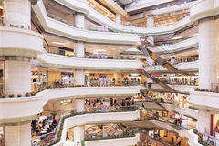 Busy shopping mall. Inside busy city retail shopping mall center with fashion stores and shops. People shopping in shop and store. Interior of modern business Stock Photo