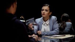 Interrogador atractivo de la señora que demuestra pruebas sangrientas del cuchillo al sospechoso imágenes de archivo libres de regalías