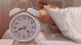 Interrupção do sono, despertador que soa perto da cama com o estudante masculino de sono filme