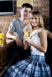 Interrupted conversation. Smiling cute blond woman and handsome brunette man behind her turned back while drinking orange juice in the bar Stock Photos