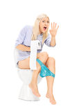 An interrupted girl sitting on a toilet Royalty Free Stock Images