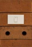 Interrupteur de lampe sur le mur de briques rouge Photo stock
