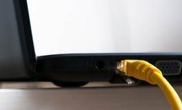 Interruptor amarillo de Internet conectado con el ordenador portátil fotografía de archivo