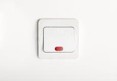 Interruptor da luz branco de ligar/desligar na parede branca com o vermelho conduzido Imagens de Stock