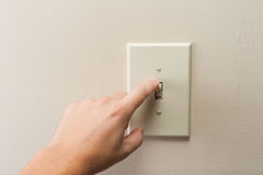 Interruptor da luz de giro da parede da mão fora foto de stock