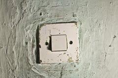 Interruptor da luz sujo velho na parede rachada velha fotografia de stock royalty free