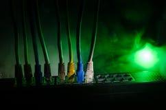 Interruptor de rede e cabos ethernet, símbolo de comunicações globais A rede colorida cabografa no fundo escuro com luzes e smo fotos de stock royalty free