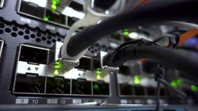 Interruptor de rede moderno com cabos Sala do servidor O diodo emissor de luz de piscamento ilumina-se perto acima Conceito 3 video estoque