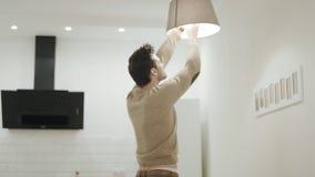 Interruptor do homem branco fora do candelabro na cozinha Indivíduo novo que torce acima da ampola video estoque