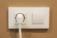 Interruptor e tomada brancos em um fundo marrom Imagens de Stock