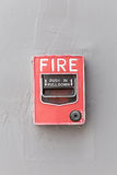 Interruptor vermelho do alarme de incêndio na parede exterior do cimento do buil comercial foto de stock