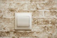 Interruttore della luce sul muro di mattoni d'annata a casa fotografie stock