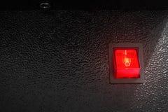 Interruttore di accensione rosso su fondo scuro Bottone di controllo elettrico fotografia stock libera da diritti