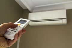 Interruttore di comando del holdind della mano del condizionatore d'aria domestico fotografia stock libera da diritti