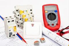Interruttori automatici, multimetro digitale Materiale elettrico, protezione e controllo, fondo bianco immagine stock libera da diritti