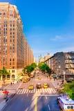 A interseção de NYC aglomerou-se com povos ocupados, carros e os táxis amarelos Tráfego icônico e negócio diário da rua em Manhat Fotografia de Stock