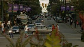 Intersección con los coches, las bicicletas y los peatones de la abundancia almacen de video