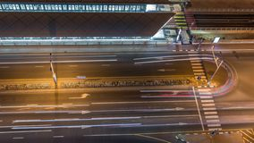 Intersection with cars and tram stop with railway aerial view from above night timelapse in Dubai Marina. Crossroad with traffic lights stock footage