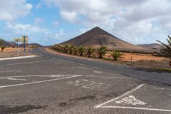 Intersection in dry volcanic landscape. Street intersection in dry volcanic landscape with mountain range in background Stock Image